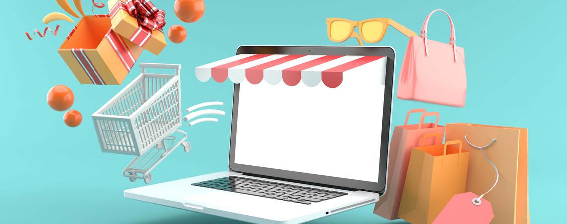 Laptop mit Einkaufstüten und Einkaufswagen