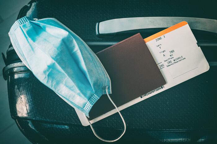 Maske und Reisepass mit Flugticket liegen auf Koffer