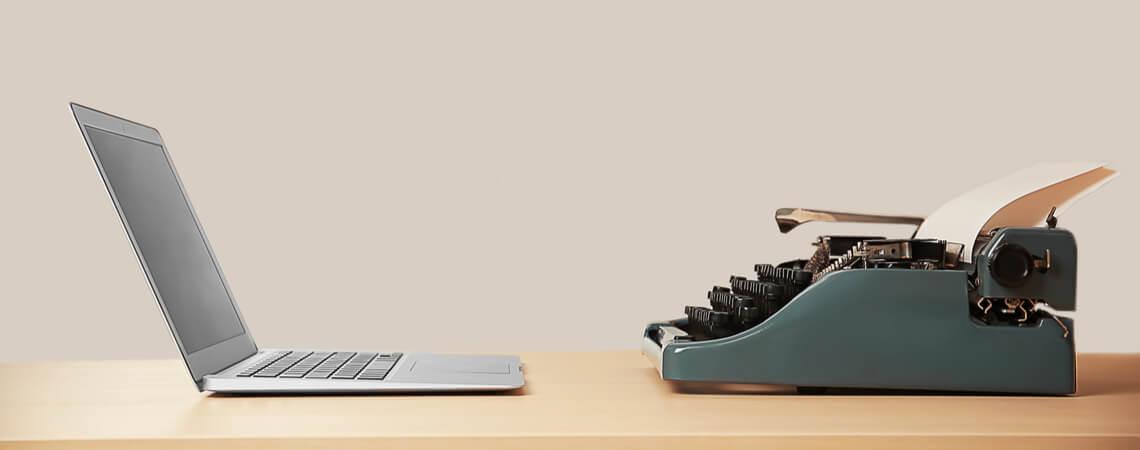 Alte Schreibmaschine und Laptop auf dem Tisch