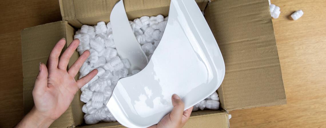 Zerbrochener Teller über Paket