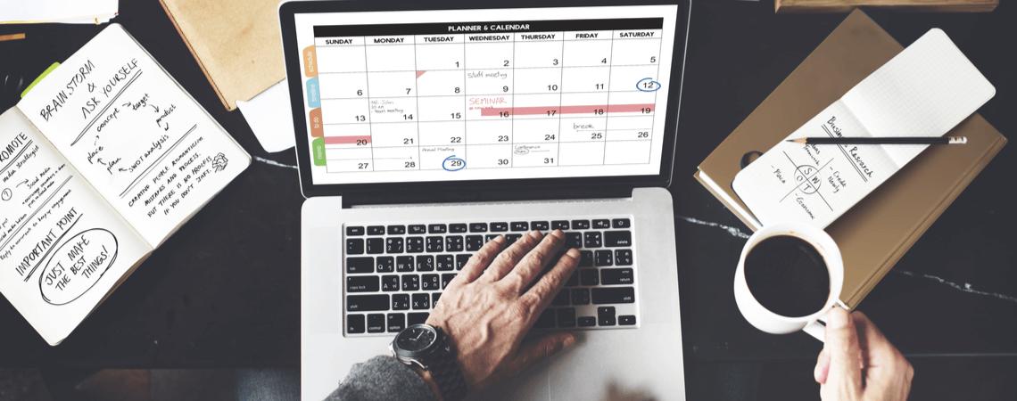 Händler am Laptop mit Kaffee und Kalender