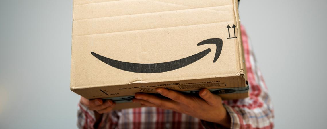 Mann trägt Amazon-Paket