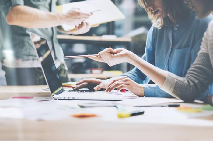 StartUp: Junges Team an einem Tisch mit Laptop