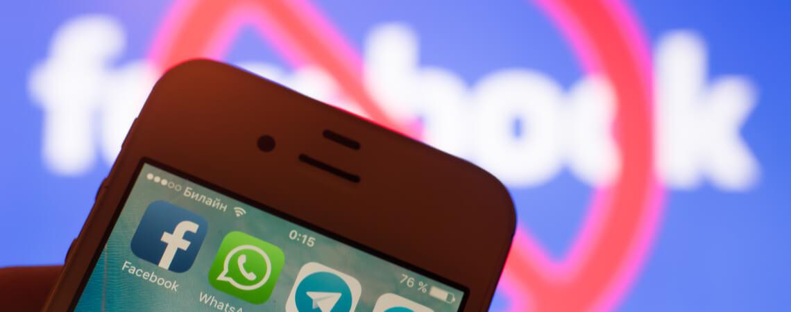 Smartphone mit verschiedenen Kommunikations-Apps. Dahinter Facebook mit einer Sperrscheibe.
