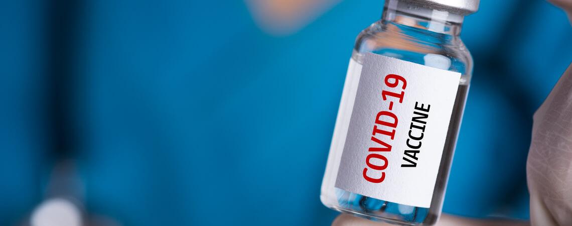 Ärztin hält Flasche mit Corona-Impfstoff in der Hand